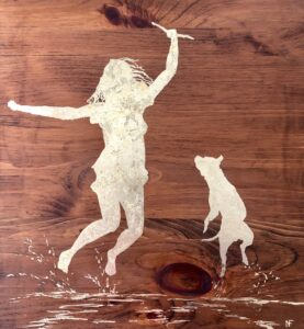 Woman and her pet dog playing in the water and leaping for fun